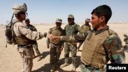 ທະຫານມາຣິນຂອງ ສຫລ (ຊ້າຍ) ຄົນນຶ່ງຈັບມືກັບທະຫານກອງທັບແຫ່ງຊາດອັຟການິສຖານ ໃນຂະນະທີ່ມີການຝຶກຊ້ອມທະຫານໃນແຂວງ Helmand ຂອງອັຟການິສຖານໃນວັນທີ 15 ກໍລະກົດ 2017