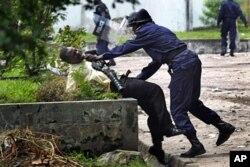 Un partisan de Tshisekedi malmené par un policier congolais devant le QG de l'UDPS à Kinshasa (8 déc. 2011)