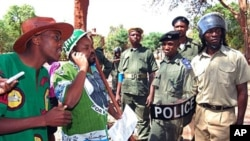 Zambia Police prevent the Patriotic Front (PF) national youth secretary, Eric Chanda (2NDL) and Patriotic Front and United Party for National Development (UPND) youth chairman Brian Hapunda (1stL)) from protesting at the Chinese Embassy in Lusaka against