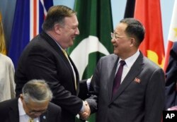 FILE - U.S. Secretary of State Mike Pompeo, left, greets North Korea's Foreign Minister Ri Yong Ho as they prepare for a group photo at the 25th ASEAN Regional Forum Retreat in Singapore, Aug. 4, 2018.