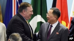 FILE - U.S. Secretary of State Mike Pompeo, left, greets North Korea's Foreign Minister Ri Yong Ho at the 25th ASEAN Regional Forum Retreat in Singapore, Aug. 4, 2018. President Donald Trump on Aug. 24 called off a visit to North Korea by Pompeo because of what the president felt was a lack of progress in denuclearization talks.
