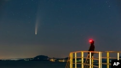 The Comet Neowise or C/2020 F3 is seen before sunrise over Balatonmariafurdo, Hungary, Tuesday, July 14, 2020. It passed closest to the Sun on July 3 and its closest approach to Earth will occur on July 23. (Gyorgy Varga/MTI via AP)