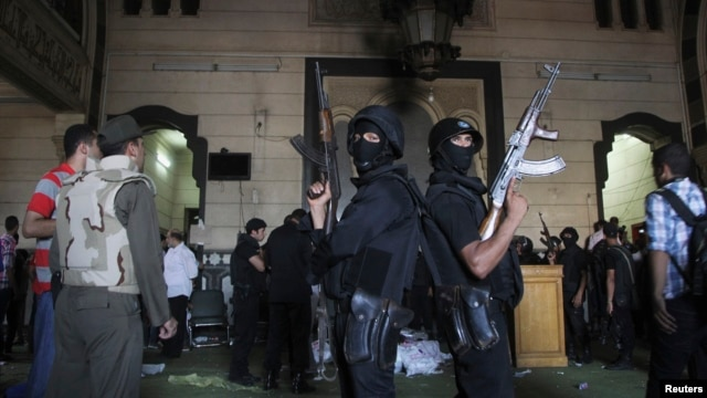 Policemen stand guard inside a room of the al-Fath mosque when supporters of deposed Egyptian President Mohamed Morsi exchanged gunfire with security forces inside the mosque in Cairo, Aug.t 17, 2013