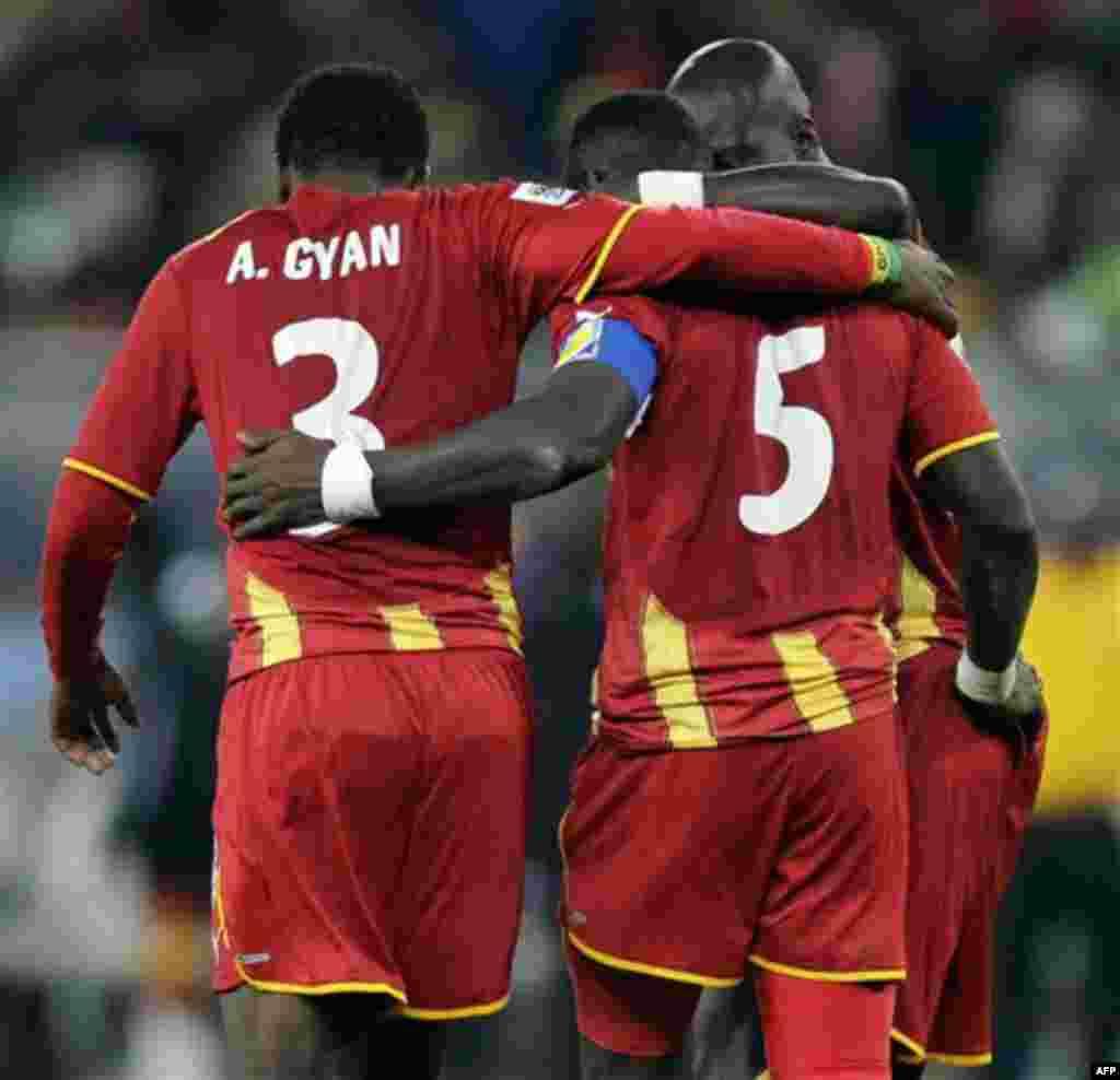 Джон Менса (Гана), в центре, утешает Асамоа Гьяна после пропуска пенальти во время матча между Уругваем и Ганой в «Футбол-Сити» в Йоханнесбурге, Южная Африка. Пятница, 2 июля 2010 года. После Матч закончился 1-1 в, Уругвай выиграл 4:2.(Фото АП / Luca Брун