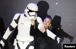 "FILE - Carrie Fisher poses for cameras as she arrives at the European Premiere of ""Star Wars, The Force Awakens"" in Leicester Square, London, Dec. 16, 2015."