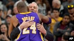 Gregg Popovich, entraîneur des San Antonio Spurs, et Kobe Bryant (24), pivot des Lakers de Los Angeles avant un match de basketball, à San Antonio, le 6 février 2016. (AP Photo/Darren Abate)