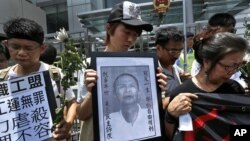 Những người phản đối cầm bức ảnh của ông Lý Vượng Dương trong cuộc biểu tình trước văn phòng liên lạc của chính phủ Trung Quốc