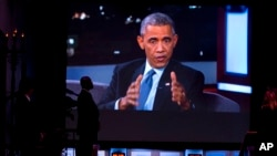 Seorang agen Dinas Rahasia AS menyaksikan layar yang memperlihatkan siaran langsung acara bincang-bincang Jimmy Kimmel Live yang menampilkan Presiden Barack Obama (12/3). (AP/Jacquelyn Martin)