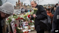 Mourners following the Russian tradition of memorializing a person nine days after a death lay flowers and votive candles at the place where Boris Nemtsov was gunned down near the Kremlin, in Moscow, on Saturday, March 7, 2015.