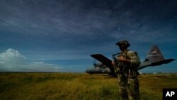 FILE - U.S. Army Spc. Kevin Martin provides security for a 75th Expeditionary Airlift Squadron cargo plane during unloading operations at an unidentified location in Somalia, June 28, 2020.