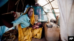 FILE - Aid workers have expressed alarm at poor conditions in South Sudan refugee camps. A woman and baby shelter in a makeshift tent at the Kalma camp in this photo released by United Nations African Union Mission in Darfur, Sudan, March 9, 2014.