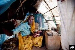 Một người phụ nữ và một em bé trong chiếc lều trú ẩn tạm thời ở trại tỵ nạn Kalma, Darfur, Sudan