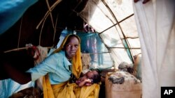FILE - Aid workers have expressed alarm at poor conditions in South Sudan refugee camps. A woman and baby shelter in a makeshift tent at the Kalma refugee camp.