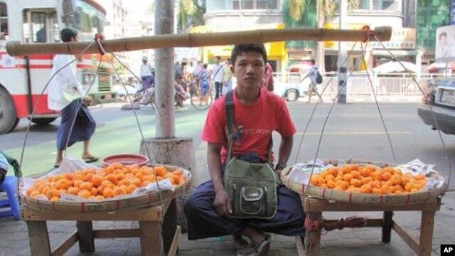 Boy sells fruit on sidewalk in Rangoon, Burma, December 5, 2011