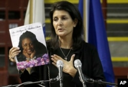 FILE - South Carolina Gov. Nikki R. Haley holds a photo of Rev. DePayne Middleton-Doctor as she speaks during a memorial service in Charleston, South Carolina, June 17, 2016, honoring those killed, including Middleton-Doctor, in the 2015 shooting at the Mother Emanuel AME Church.