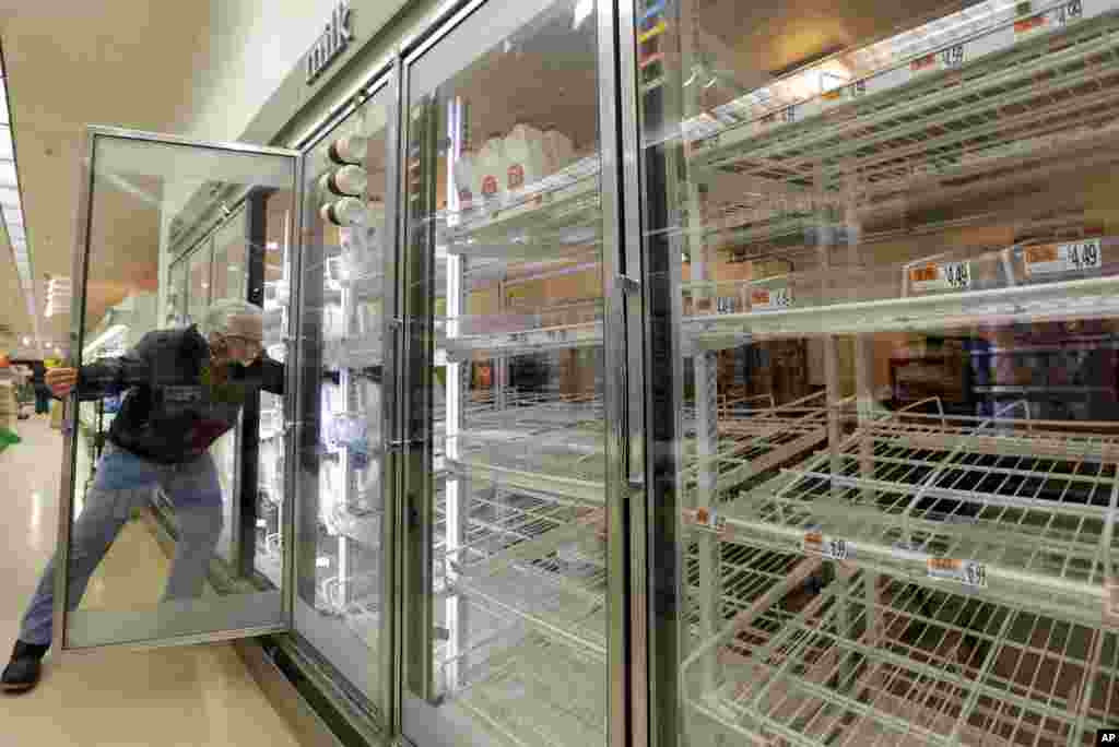 Jack Percoco of Cambridge, Massachusetts, reaches into depleted shelves for milk at a supermarket in Somerville, Massachusetts, Feb. 8, 2013.