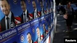 A woman walks past election posters ahead of the parliamentary elections in Tbilisi, Georgia, Oct. 6, 2016. To the surprise of many, a small pro-Russia party garnered enough votes to pass the 5 percent threshold required for representation in the country's legislature.
