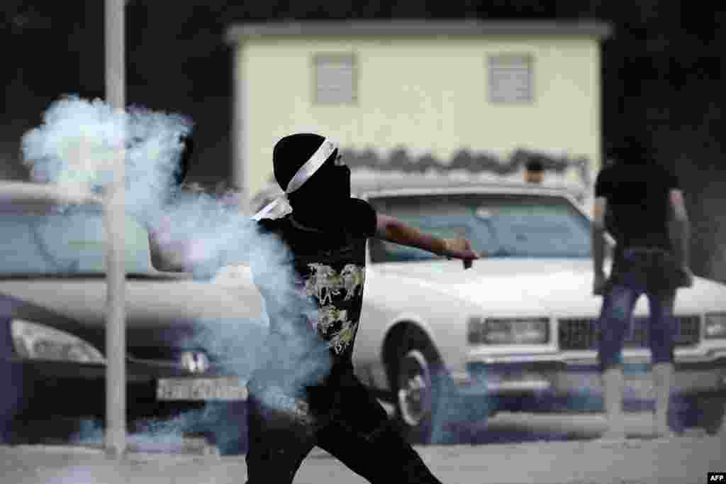A Bahraini protester throws back a tear gas canister during clashes with riot police following an anti-regime demo heading to 'Pearl Square' after a religious procession marking Ashura in the village of Daih, Bahrain.