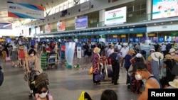 Les touristes portent des masques de protection en attendant l'enregistrement pour le départ à l'aéroport de Da Nang, Vietnam le 26 juillet 2020. Tran Le Lam / VNA via REUTERS.