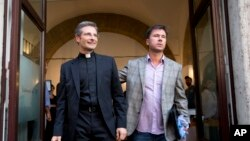 Monsignor Krzysztof Charamsa (l), and his boyfriend Eduard, surname not given, pose for a photo as they leave a restaurant after a news conference in downtown Rome, October 3, 2015.