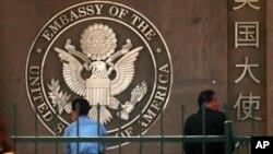 駐北京的美國大使館的標徽和中文名字。旁邊有人等待申請簽證。