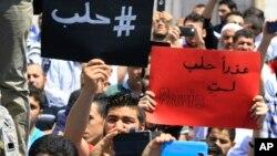 """Người biểu tình Lebanon cầm những tấm bảng tiếng Ả Rập với nội dung """"#Aleppo"""" (trái) và """"Xin lỗi, Aleppo, các bạn không phải là Paris"""" (phải) trong một cuộc biểu tình thể hiện tình đoàn kết với Aleppo ở Sidon, Lebanon, ngày 06 tháng 5 năm 2016."""