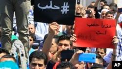 """ພວກປະທ້ວງຊາວເລບານອນ ຖືປ້າຍຂຽນເປັນພາສາອາຣັບ ທີອ່ານວ່າ """"#Aleppo,"""" ຢູ່ເບື້ອງຊ້າຍ, ແລະ """"ເສຍໃຈ, Aleppo, ເຈົ້າບໍ່ແມ່ນ Paris,"""" ຢູ່ເບື້ອງຂວາ."""