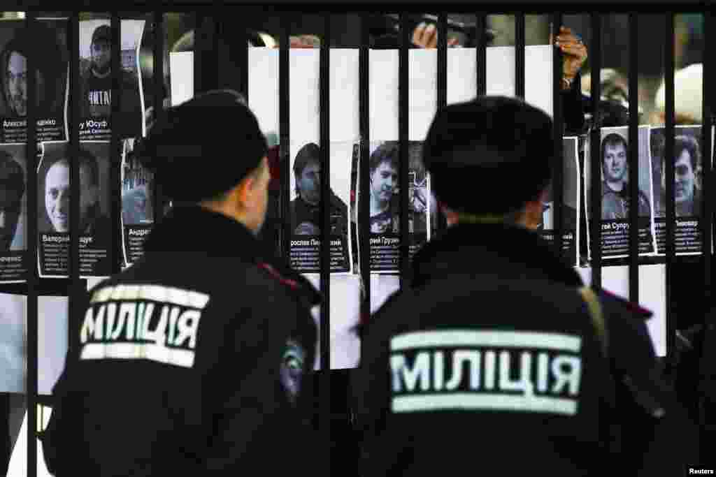 Police look at portraits of missing political activists and journalists that protesters pasted on the gate of the Crimean Interior Ministry in Simferopol, March 18, 2014.