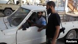 Un salafista del grupo Ansar al-Sharia revisa una camioneta a la entrada de un hospital en Bengasi.