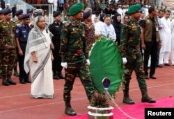 Bangladesh's Prime Minister Sheikh Hasina pays homage in front of the coffins of the victims who were killed in the attack on the Holey Artisan Bakery and the O'Kitchen Restaurant, during a memorial ceremony in Dhaka, July 4, 2016.