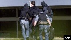На сделанной в пятницу фотографии показан момент ареста одого из подозреваемых.
