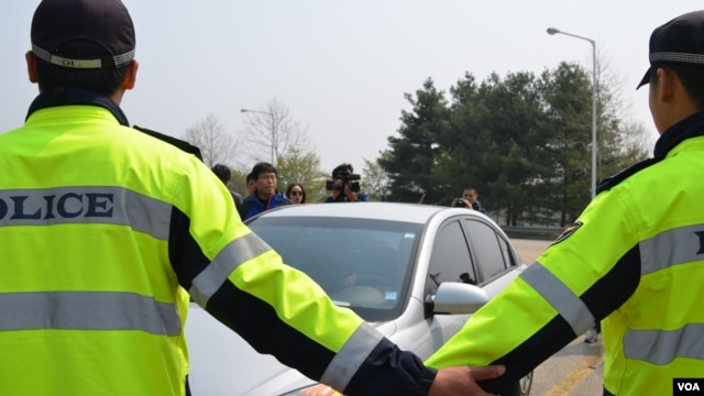 South Korean police prevent a car driven by a North Korean defector from entering site of a planned launch of balloons carrying leaflets, May 4, 2013. (R. Kalden/VOA)