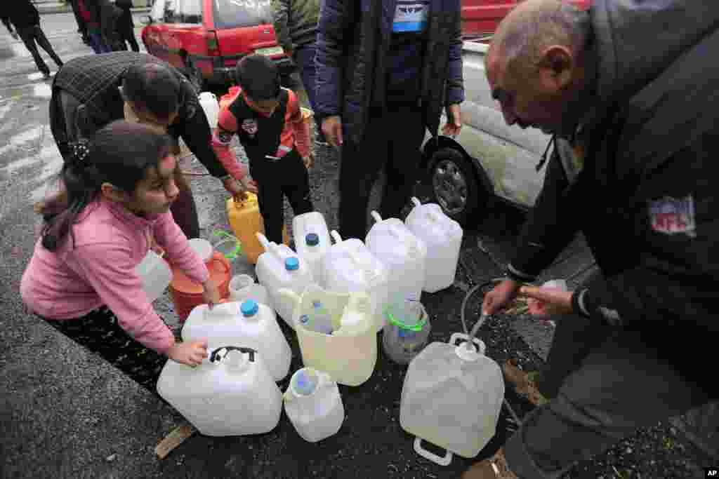 پر کردن ظرفهای پلاستیکی با آب در دمشق، پایتخت سوریه.