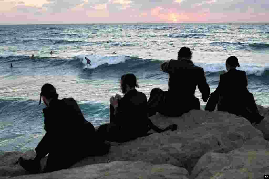 Những người Do Thái giáo phái siêu Chính thống ngồi xem người Israel lướt sóng trong dịp lễ Sukkot của người Do Thái ở thành phố cảng miền nam Ashdod của Israel, ngày 23 tháng 9, 2013.