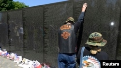 Thành viên trong nhóm 'Rolling Thunder' đặt tay lên bức tường đá hoa cương đen của Đài tưởng niệm Cựu chiến binh Việt Nam ở thủ đô Washington, ngày 25/5/2014.