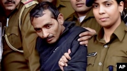 FILE - Shiv Kumar Yadav, 32 (c) a driver from the international taxi-booking service Uber, is surrounded by police as he is brought out after being produced in a court in New Delhi, India, Dec. 8, 2014.