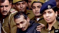 Shiv Kumar Yadav, 32 (tengah), pengemudi taksi Uber, dikawal ketat oleh polisi seusai menjalani sidang di pengadilan New Delhi, India (8/12).