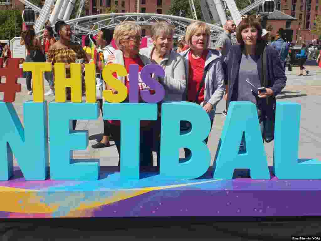 "Netball fans standing by a ""This is Netball"" sign"