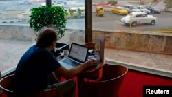 A man surfs the Internet using a wireless connection in the lobby of a hotel in Havana, Cuba, January 23, 2013.