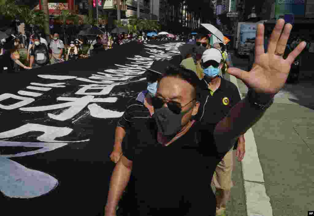 ادامه اعتراضات در هنگ کنگ؛ معترضان بنری را حمل می کنند که روی آن نوشته شده است «پلیس هنگ کنگ عمدا آدم می کشد»