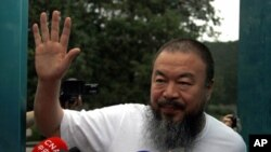 Dissident Chinese artist Ai Weiwei waves from the doorway of his studio after he was released on bail in Beijing June 23, 2011. Ai was detained in April, igniting an international uproar, but he was released on bail on Wednesday under conditions likely to