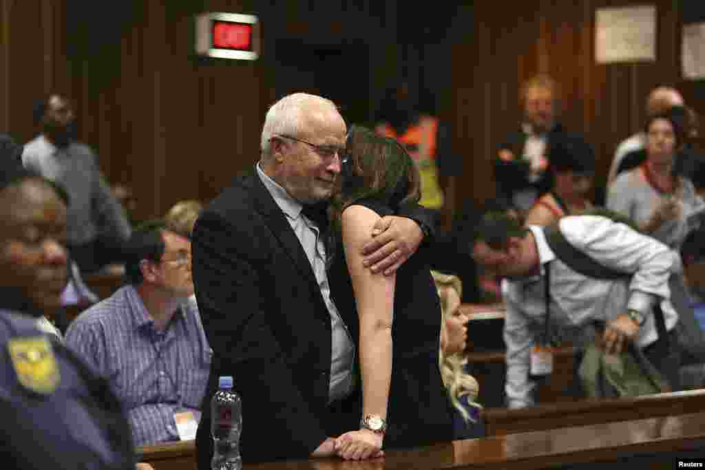 Henke Pistorius and Aimee Pistorius, the father and sister of Oscar Pistorius, embrace after the reading of the verdict by Judge Thokozila Masipa at the North Gauteng High Court in Pretoria, Sept. 12, 2014.