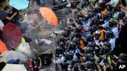 示威民众面打着雨伞对抗警察胡椒喷雾