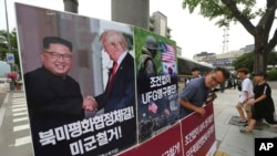 FILE - A photo showing U.S. President Donald Trump and North Korean leader Kim Jong Un is displayed as a member of People's Democratic Party stands to oppose military exercises between the United States and South Korea, near the U.S. Embassy in Seoul, South Korea, June 19, 2018. Trump warned on Aug. 29, 2018, that the United States could at any time restart joint military exercises with South Korea and Japan if progress stalled on North Korean denuclearization.