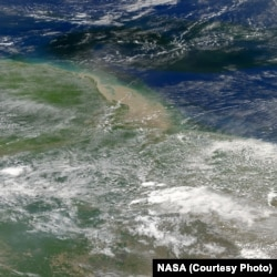 The Amazon River plume where it meets the Atlantic Ocean off Brazil's coast. River water is green. Credit NASA