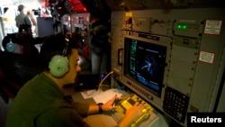 Sersan Matthew Falanga, analis elektronik udara, mengamati gambar radar di atas pesawat AP-3C Orion milik Angkatan Udara Australia dalam pencarian pesawat Malaysian Airlines penerbangan MH370 di atas Samudera Hindia (27/3).