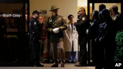 Hospital and law enforcement workers stand at an entrance to Tacoma General Hospital in Tacoma, Washington, as they wait for the body of a Tacoma Police officer who was shot and killed while answering a domestic violence call Nov. 30, 2016, to be removed from the hospital in a procession.