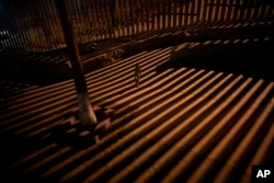 A boy plays as floodlights from the United States filter through the border wall, Jan. 11, 2019, in Tijuana, Mexico. The partial U.S. government shutdown has now become the longest closure in U.S. history as President Donald Trump and nervous lawmakers look for a way out of the mess.