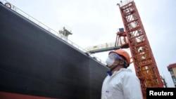 一名戴着口罩以防止冠状病毒病传播的码头工人在中国山东省青岛市的一艘油轮上卸下原油。