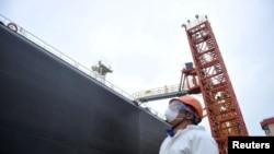 2020年3月26日,中国山东青岛港一码头工人在瞭望一油轮。